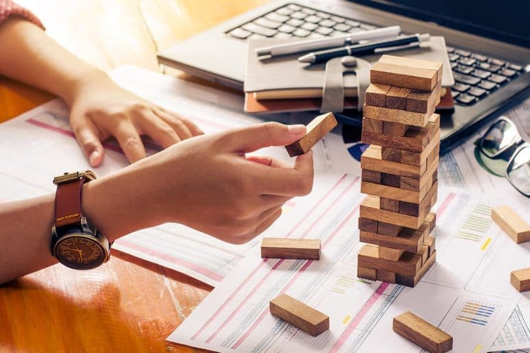Hands building tower with wooden blocks showing how companies should carry out effective vendor risk management