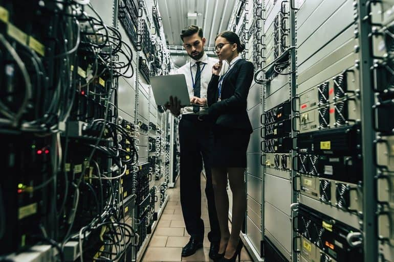 Technicians in data center examining servers showing the importance of finding legacy applications to prevent data breach