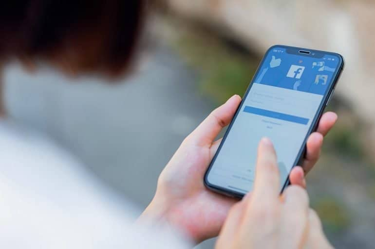 Man using Facebook on mobile showing Facebook data sharing with top mobile carriers