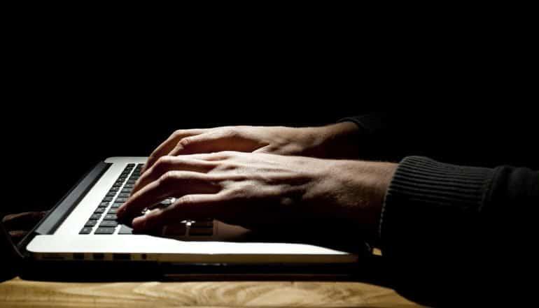 Man working on laptop in dark room showing increasing dark net hacking services targeted at enterprises