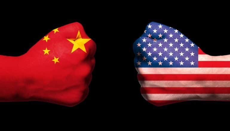 Flags of USA and China on two clenched fists showing the new draft China cybersecurity law which could block US tech firms from doing business
