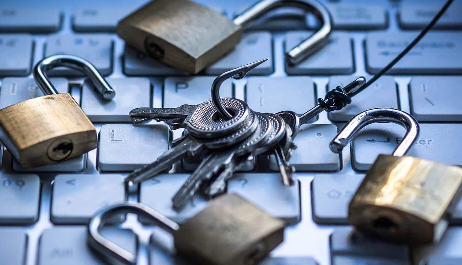 Keys on hook with opened padlocks on keyboard showing polymorphic phishing attacks making up almost half of phishing attempts