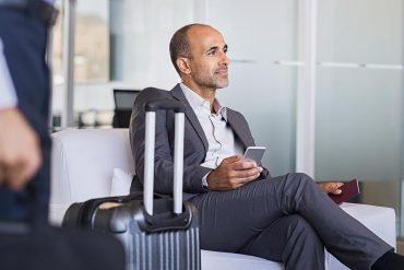 Businessman waiting in airport showing the risks of visual hacking for business travelers