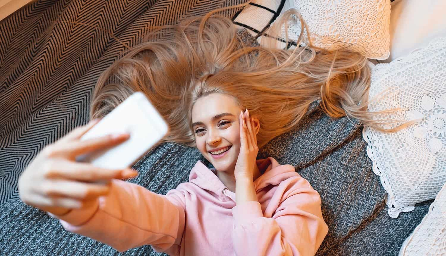 Young girl taking selfie showing FaceApp privacy seen as the type of drama we've come to expect from social media companies