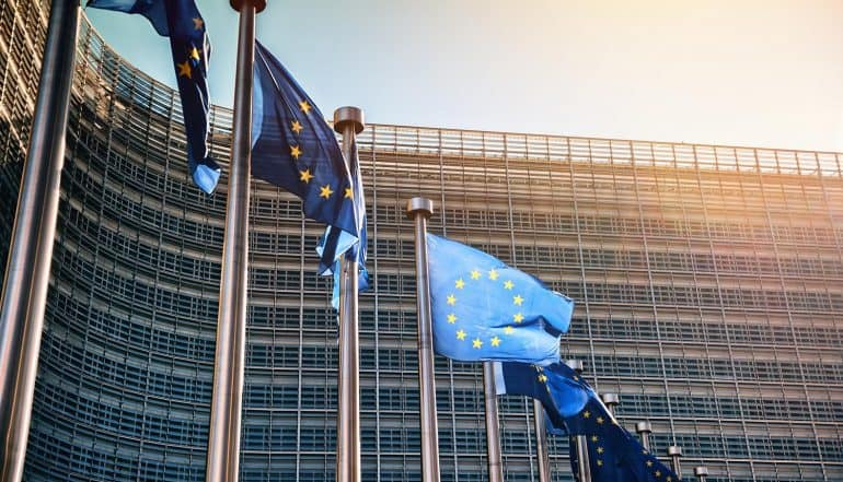 EU flags waving in front of European Parliament building showing the continuing challenges for companies to stay in compliance with GDPR