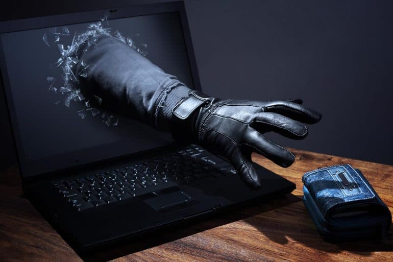 Hand stealing a purse through a laptop showing new cyber attack trends report revealed a $45 billion cyber crime industry in 2018