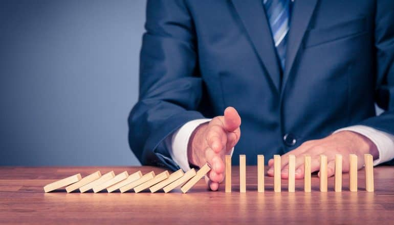 Businessman stopping domino effect showing small vendors may not be the most vulnerable targets in supply chain security