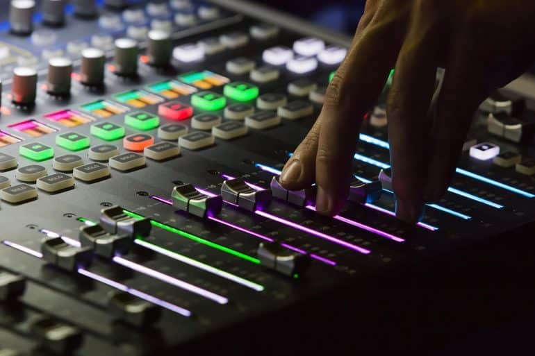 Hand on audio mixing board showing the rising use of deepfake audio to run AI cyber attacks