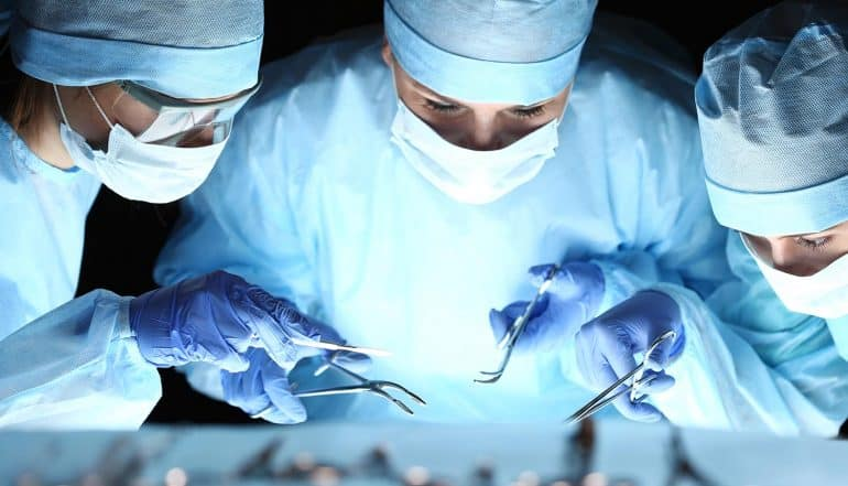 Group of surgeons working in surgical theatre showing the email security setbacks unique to healthcare