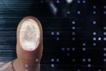 Man pressing at fingerprint scanner on virtual screen showing the data breach of biometrics database which exposed 28 million records of facial recognition and fingerprint data