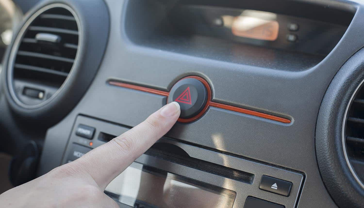 Woman inside car pressing hazard lights button showing the threats of cyber attacks on connected cars