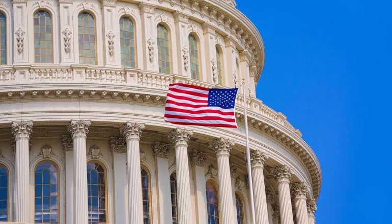 U.S. flag flying outside capitol building showing election security currently taken as high priority issue in U.S.