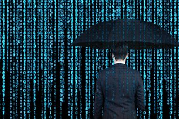 Man with umbrella against binary number background showing the risks in current cyber insurance market