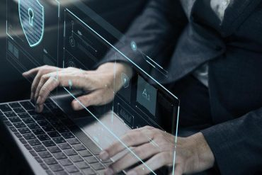 Man typing on keyboard with screen showing lock and AI showing how RPA can be used for cybersecurity