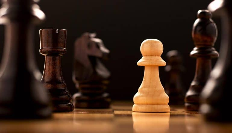 Pawns on chessboard showing the digital battleground of cyberwarfare and how nations can defense against the threats