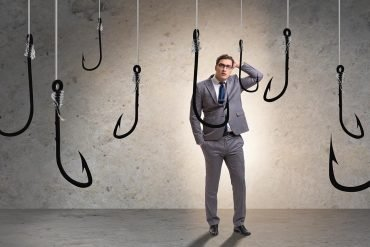 Man standing puzzled among hanging hooks showing potential uptick in phishing attacks with millions of Facebook users' phone numbers exposed in recent data breach