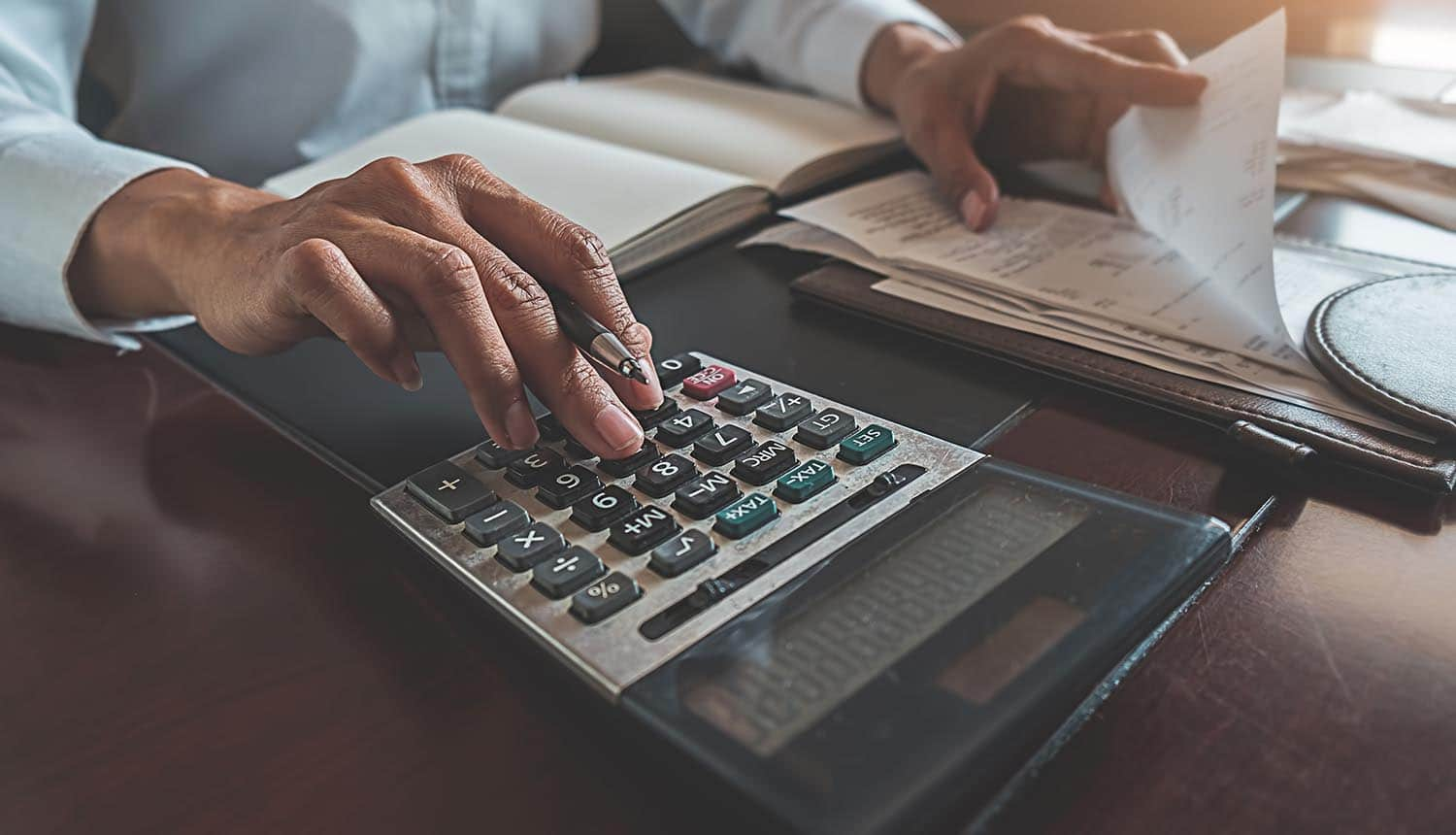 Woman using calculator to calculate bills showing how the cyber insurance payouts are encouraging more ransomware attacks