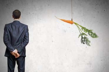 Businessman standing next to dangling carrot showing how cyber insurance providers incentivize clients to buy from specific vendors