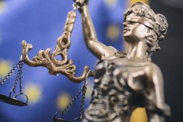 Lady Justice statue in front of E.U. flag showing recent European Court of Justice ruling that Google does not have to apply 'right to be forgotten' requests worldwide