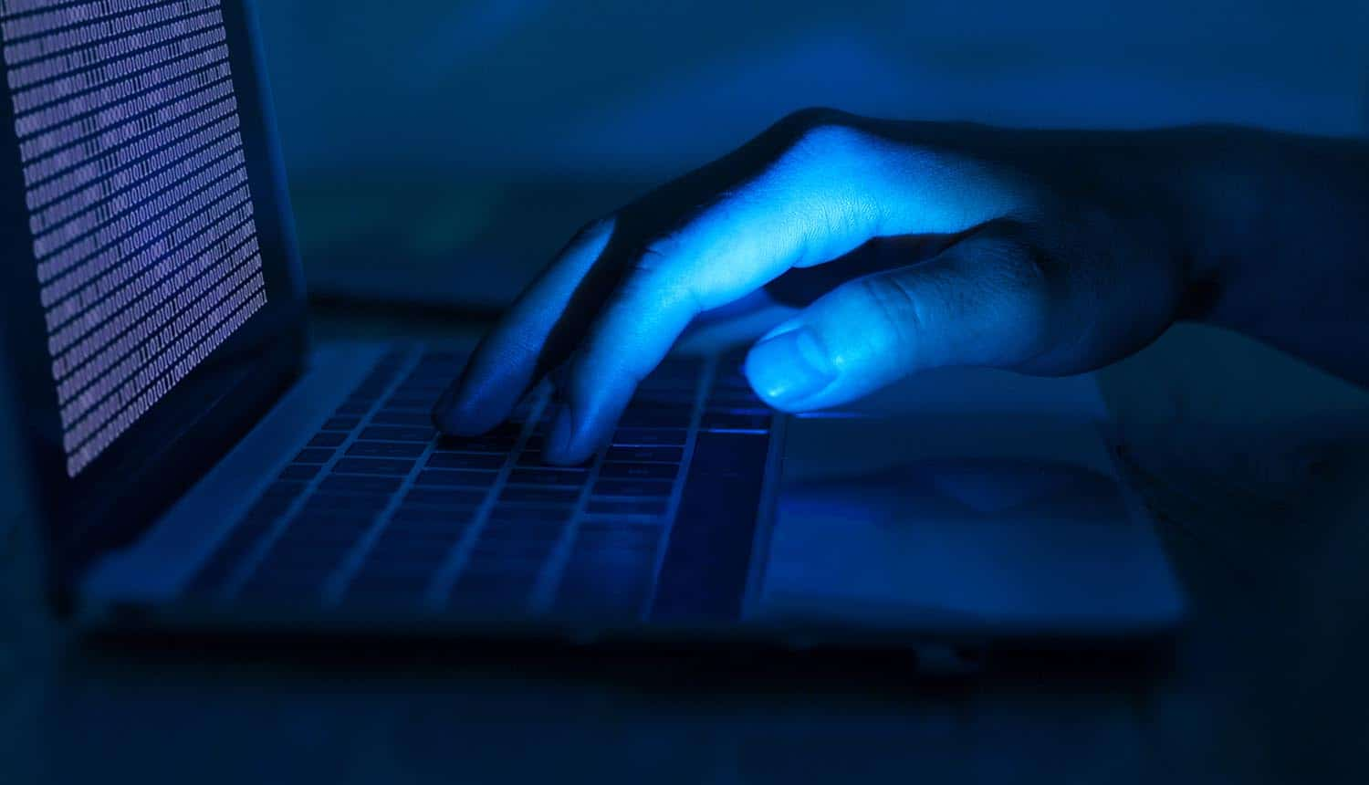 Hacker using laptop showing the Europol report on organized cybercrime highlighting crypto ransomware as top threat