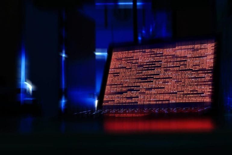 Laptop displaying red code in a dark room showing the struggle on national ransomware epidemic faced by U.S. municipalities and local government agencies