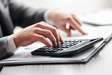 Man using calculator to calculate costs showing initial CCPA compliance costs of $55 billion estimated in new report
