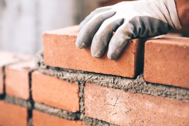 Hand laying bricks for a wall showing the need for multiple firewalls
