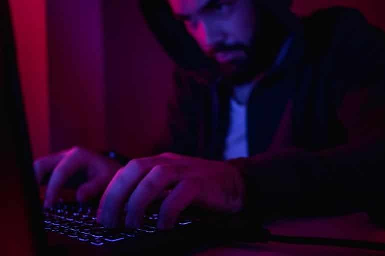 Hacker working on laptop showing Russian hackers piggybacking on exploits of Iranian hackers