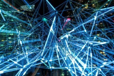 Laser lights speeding through city scape showing how technology is driving down costs everywhere