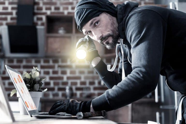 Hacker holding a torch and typing on laptop showing the effects of corporate identity theft on businesses