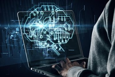 Side view of hands using laptop with glowing circuit brain hologram showing Alibaba fending off cyber attacks using AI