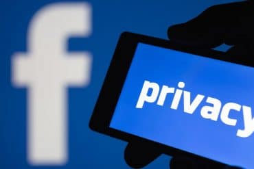 Privacy text on mobile phone against Facebook logo background showing a Facebook privacy breach which involves developers