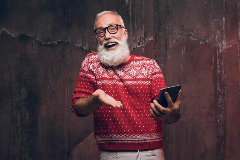 Happy senior man gesticulates in a Christmas sweater showing the gift of peace of mind