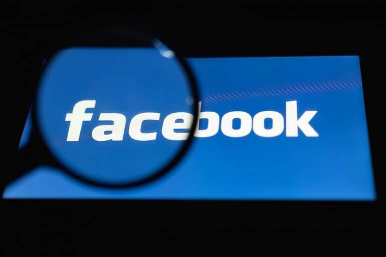Magnifying glass over Facebook logo showing leaked Facebook documents revealing how company used personal data for competitive advantage