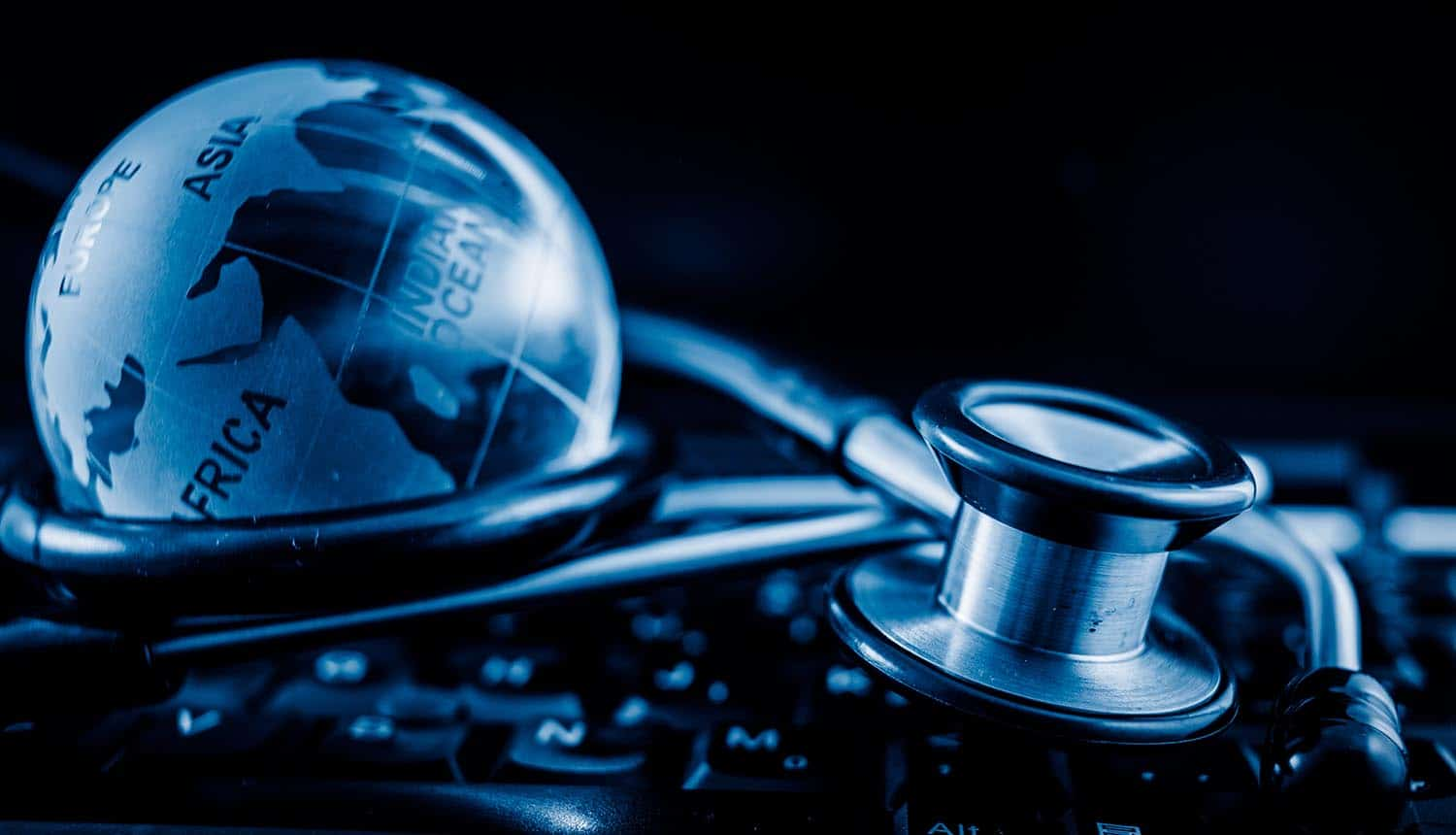 Glass globe and stethoscope on a computer keyboard showing health websites sharing medical data with advertisers