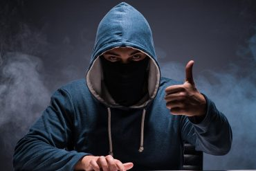 Hacker working in dark room showing need to be prepared against advanced persistent threats