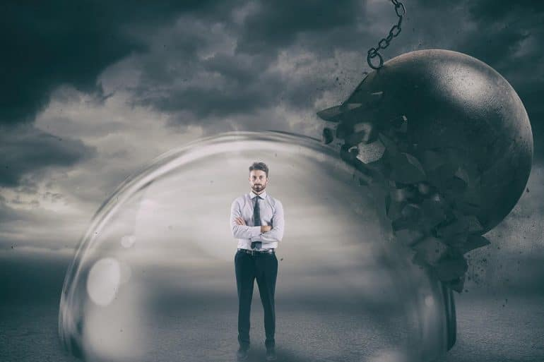 Businessman inside a shield dome during a storm showing the need to have a good crisis plan to manage threats