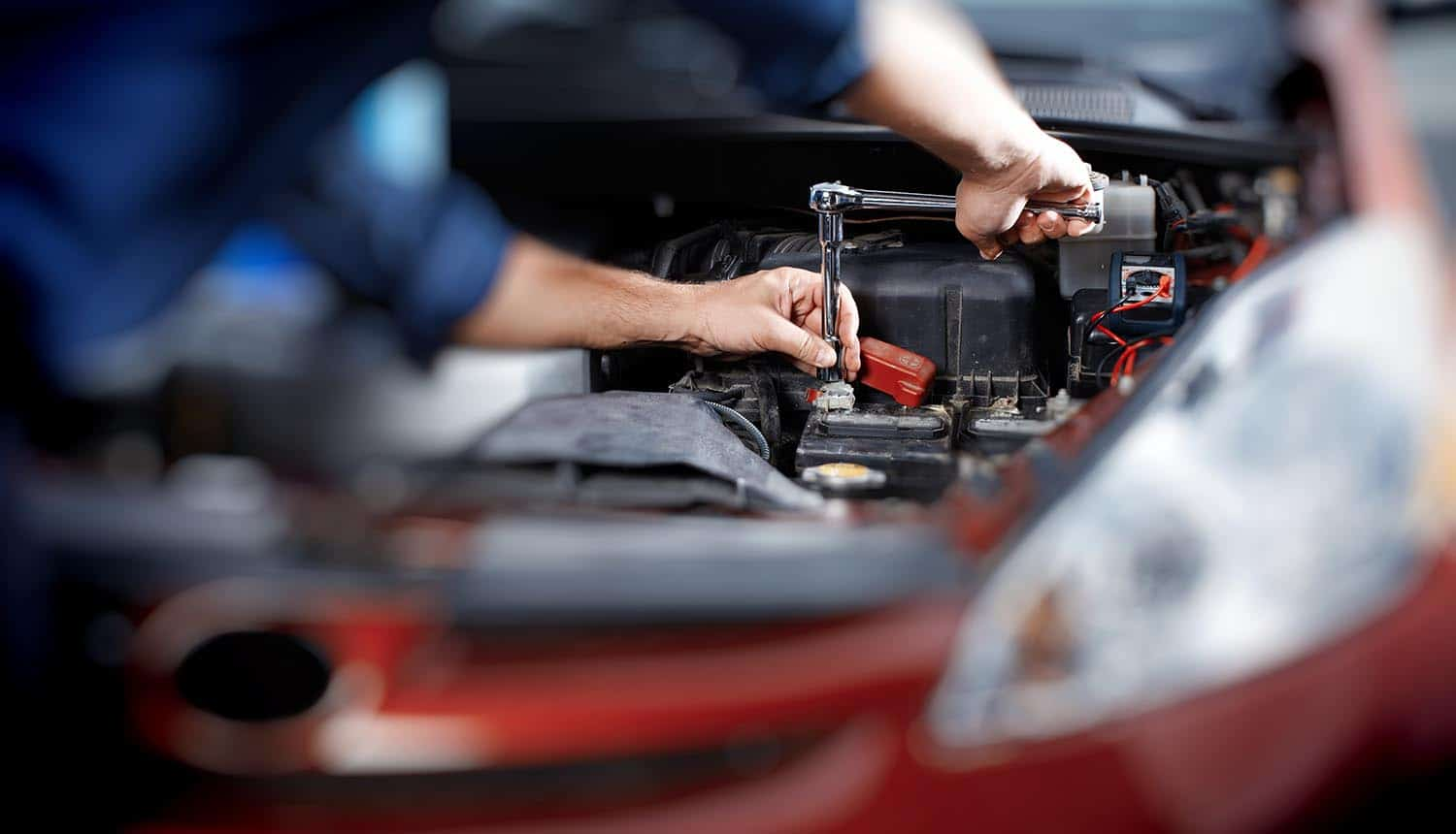 Mechanic working on car engine showing the warning from FBI that U.S. automotive industry is targeted by hackers