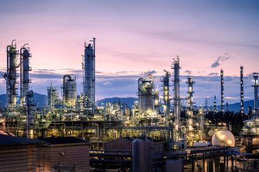 Petroleum plant on sky twilight background showing Iranian hackers APT33 threatening ICS security