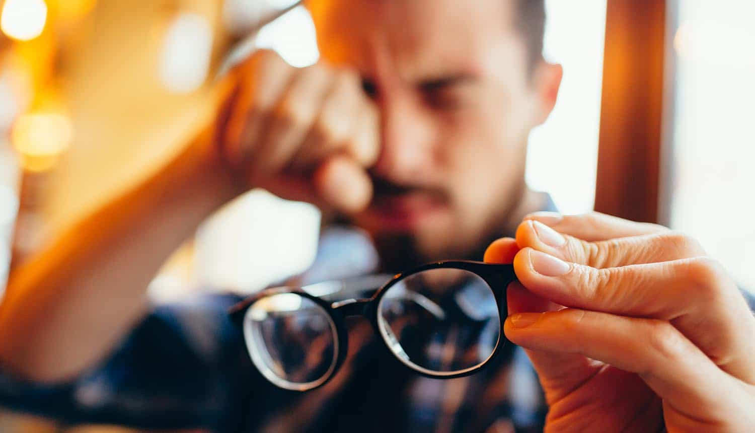 Man holding eyeglasses on one hand and rubbing his eyes with another showing how Americans are concerned and confused over personal data collection and data privacy