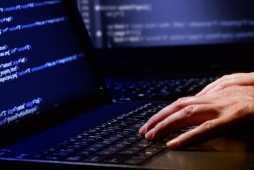 Man coding on laptop showing the implication of HiQ vs. LinkedIn case on automated web scraping