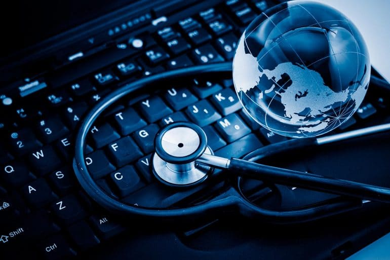 Glass globe and stethoscope on a computer keyboard showing the need for healthcare industry to have an active cybersecurity community