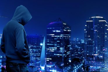 Silhouette of hooded hacker standing on the top of the building at night showing cyber security threats to business