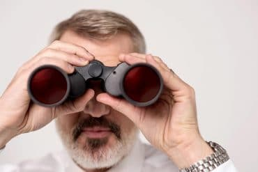 Man seeing through binoculars showing cyber security landscape in 2020 and beyond