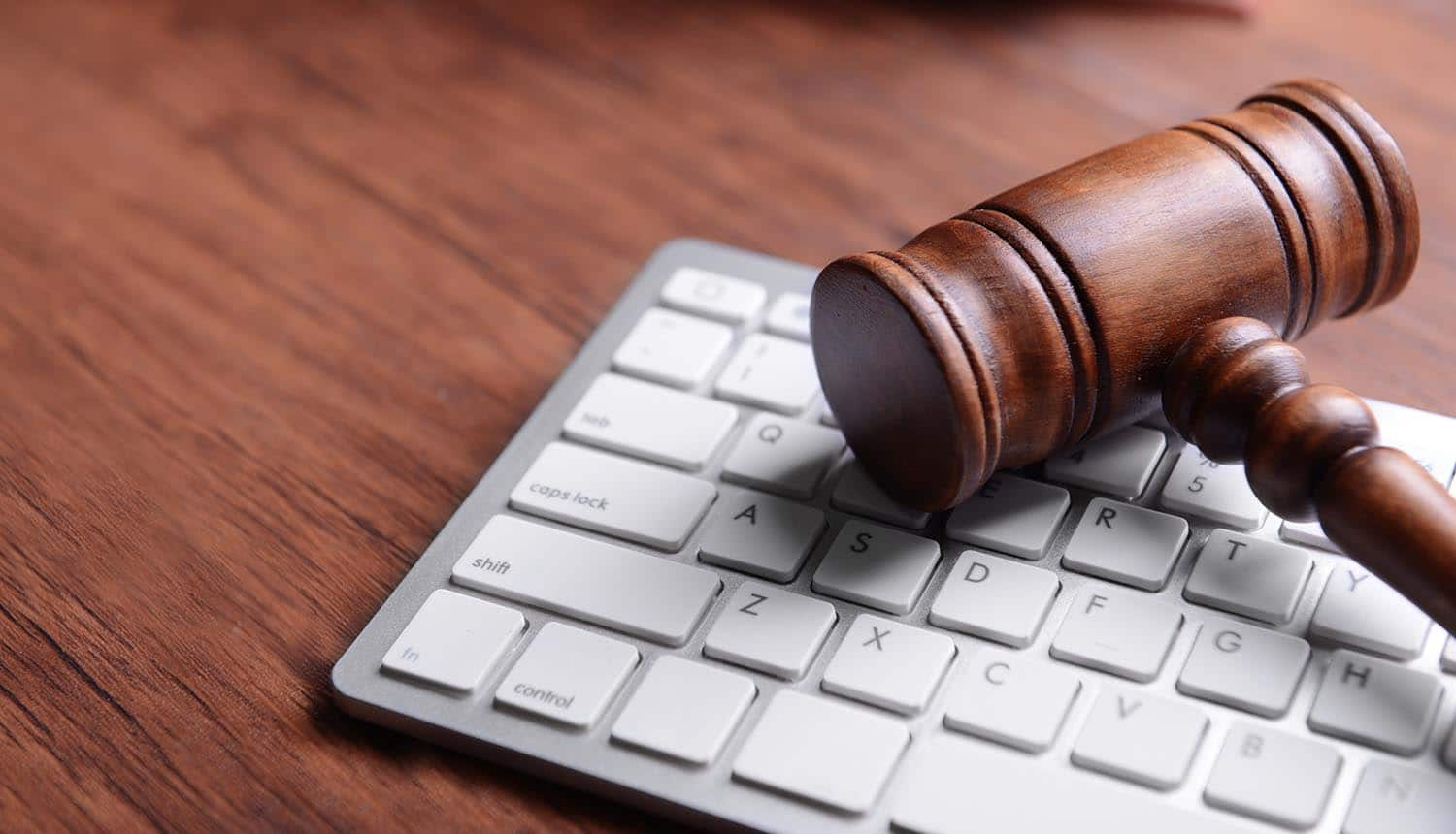 Wooden gavel and keyboard on desk showing the steps to take in anticipation of CCPA litigation in 2020