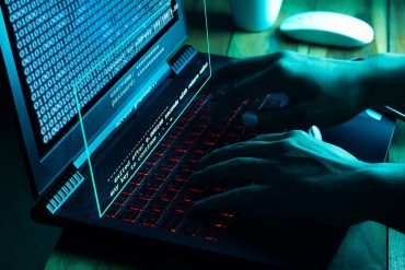 Hacker working on laptop showing Botnet owner reveals Telnet access credentials for over half a million devices