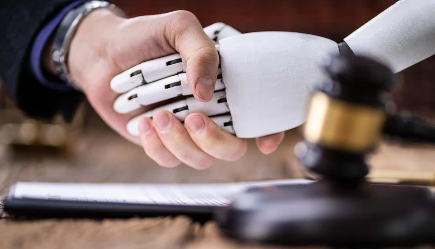 Robot shaking hands with judge near gavel showing the need for AI regulation