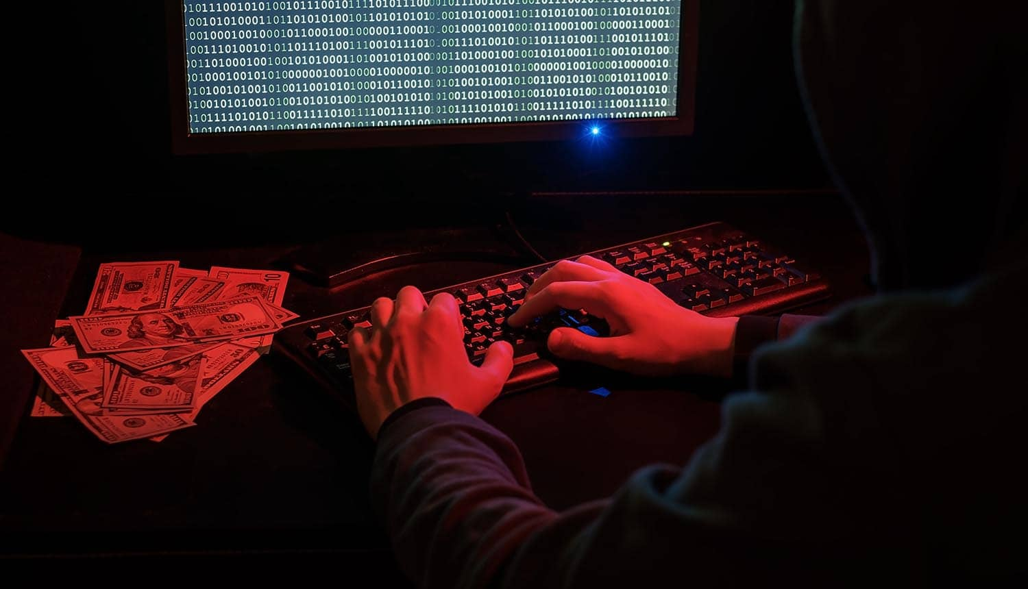Man in hood working on computer next to pile of cash showing the financial impact of phishing scam