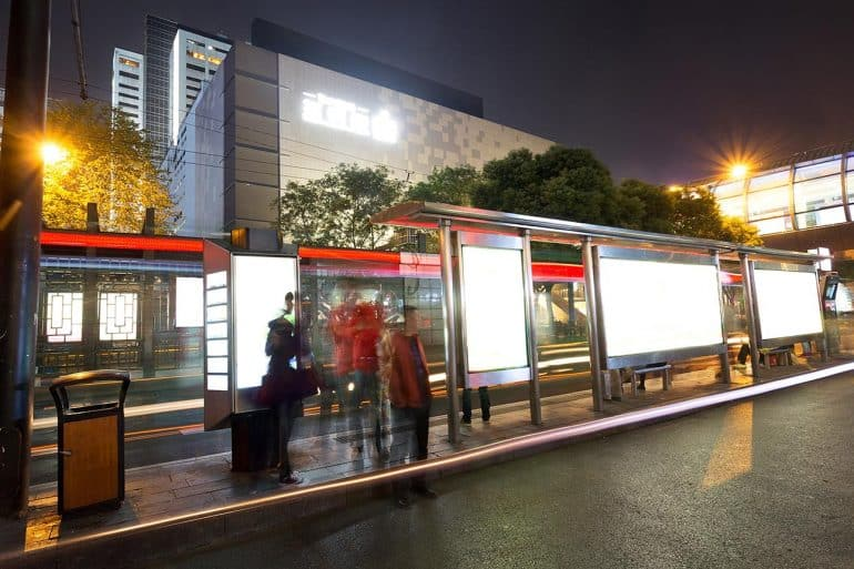 Blank billboard on bus stop at night showing possible investigation in ad blockers