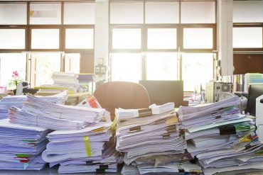 Office desk with pile of documents showing top five ways to survive the deluge of data subject requests